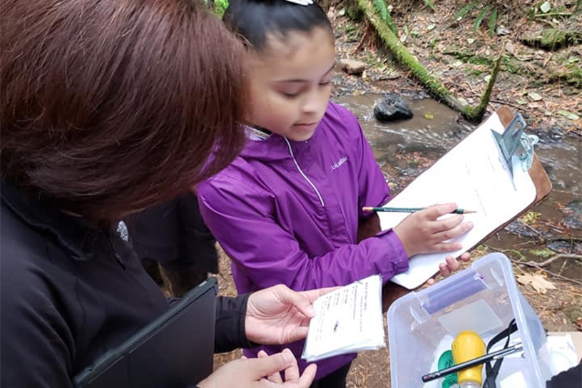 young girl with a clipboard reporting data from her forest educational program to her supervisor